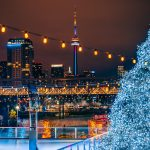 Christmas tree and skating rink in front of the Toronto skyline